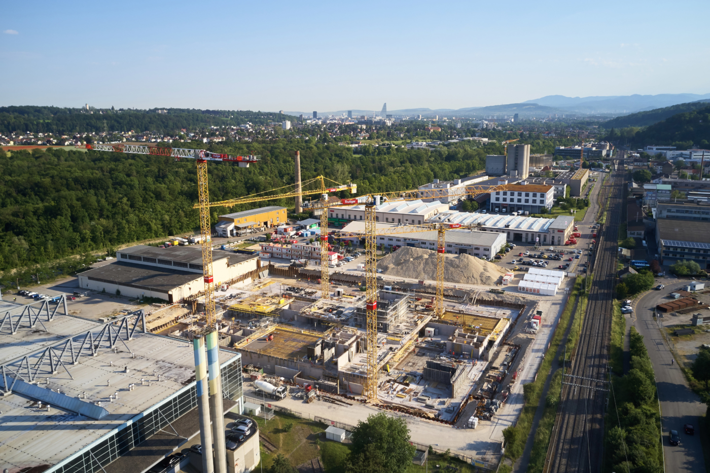 Photos for this media folder, Aerial view of the uptownBasel construction site from 5 June 2019, looking from the Sundgauer Viaduct towards the city of Basel. The site just outside the university city of Basel is being developed into a competence centre for Industry 4.0.  © Copyright Bela Böke, arbel gmbh  Digitale Medienmappe «Laying the uptownBasel foundation stone: a quantum leap for the industry», uptownBasel